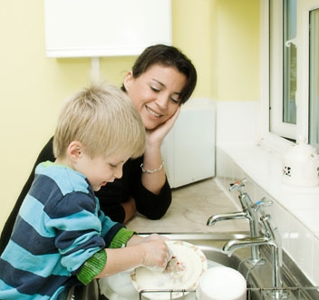 Woman and child wash dishes