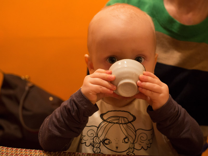 Baby drinking from a small cup