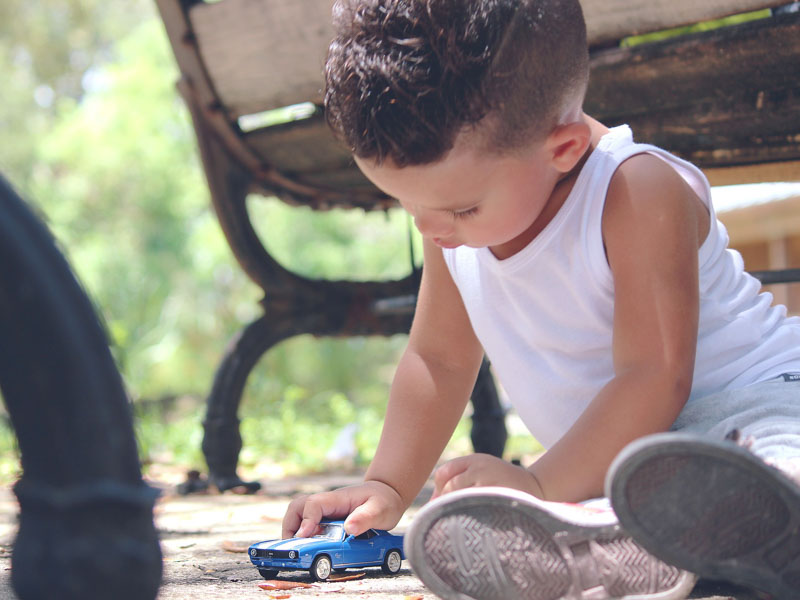 Child sits on ground and plays with toy car