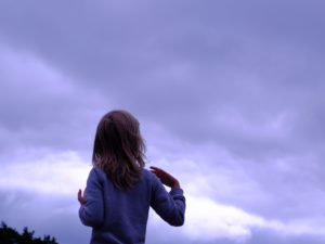 Child looking up at clouds in sky