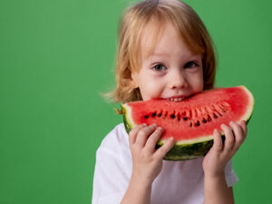 Child biting watermelon
