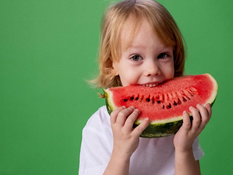 Child biting watermelon